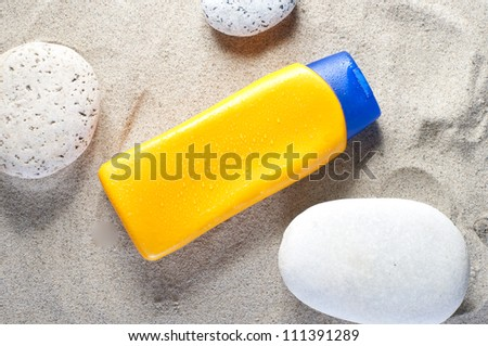 Suntan cream on sand beach background.