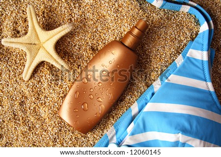 suntan lotion container on sand