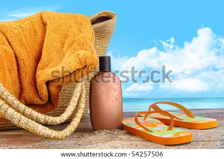 Suntan lotion, flip flops with towel at the beach - stock photo