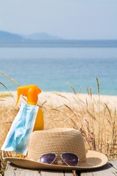 suntan lotion, sunglasses, hat and medical mask on the beach, prevention against viruses and infections on summer vacations