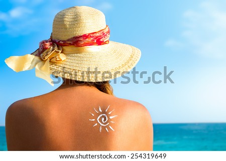 Suntan lotion woman with sunscreen solar cream over ocean background #254319649
