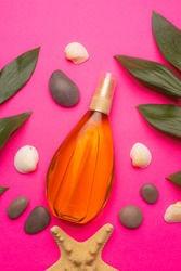 Suntan oil on a pink background . Suntan oil and green leaves. Vacation. Protect your skin from the sun. Uniform tan. Article about vacation. Pink background. Copy space