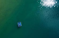 Suntanning couple on floating platform aerial top view. Bright sn reflecting in green lake waves. Peruca Lake, Dalmatia, Croatia