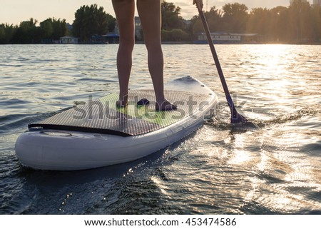 SUP confident woman swimsuit standing with a paddle on the surfboard, legs
