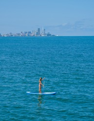SUP Stand up paddle board. Blond girl sailing on paddle board in blue sea. Woman on summer holidays vacation lifestyle. Batumi city on background. Georgia country.