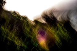 Super abstract, motion-blurred, warm green landscape with a touch of multicolor under blown-out sky pattern background texture