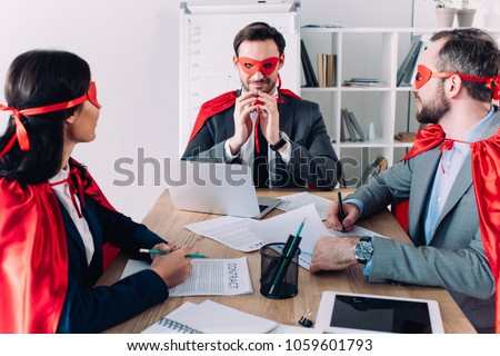 super businesspeople in masks and capes at meeting in office #1059601793