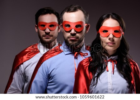 super businesspeople in masks and capes looking at camera isolated on grey #1059601622