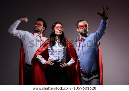 Photo of super businesspeople in masks and capes showing superpower isolated on grey
