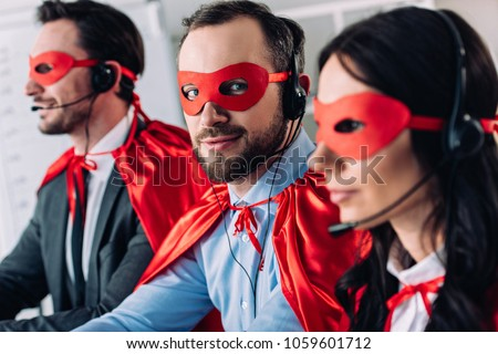 super businesspeople in masks and headsets supporting customers in call center #1059601712
