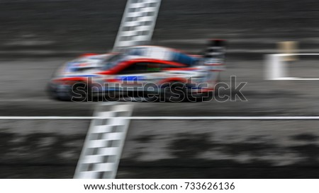 Super car race on the international race track crossing finish line with motion blur.