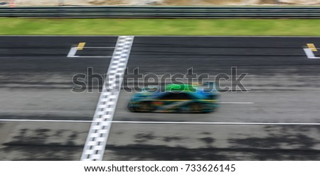 Super car race on the international race track crossing finish line with motion blur. #733626145