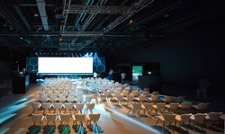 Super conference hall with white chairs and colored illumination and blank screen