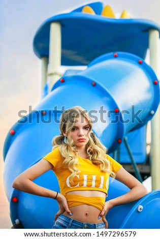 Super cool urban rebel teen girl with wavy long blonde hair posing on playground outdoor.Teen fashion editorial photography