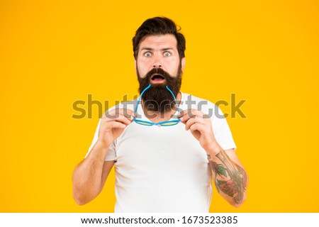 Super crazy surprise. Crazy hipster keep mouth open yellow background. Surprised bearded man hold glasses with crazy look. Barbershop. Fashion and style. Crazy and shocking.