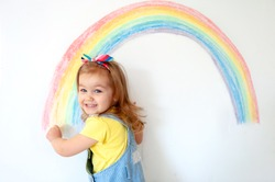 Super cute little girl drawing rainbow on white wall at home. Sign of hope. Quarantine. Coronavirus. Smiling child looking in camera. Stay at home.