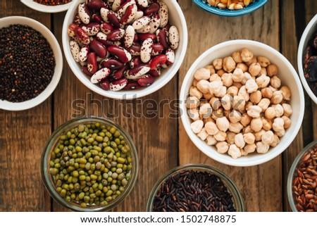 Super food. Raw cereals, grains, legumes, chickpeas, corn, quinoa, hemp, rice against rustic background top view. Vegetarians.