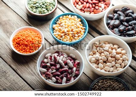 Super food. Raw cereals, grains, legumes, chickpeas, corn, quinoa, hemp, rice against rustic background. Vegetarians.