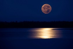 Super full moon in night sky and reflected in water wavy surface,Full moon festival