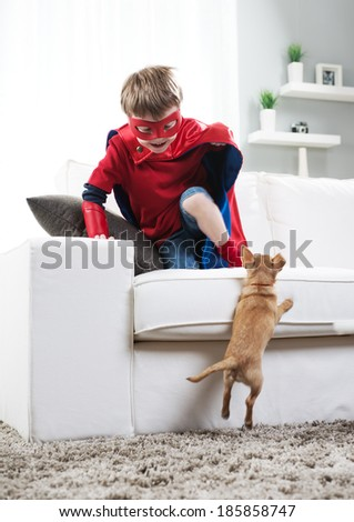 Super hero boy and chihuahua dog playing in the living room.
