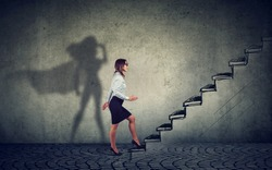 Super hero business woman stepping up on stairs climbing to success on gray wall background
