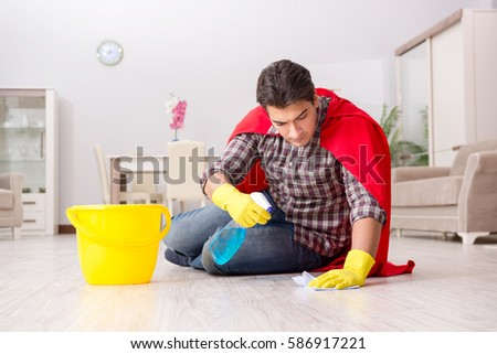 Super hero husband cleaning floor at home #586917221