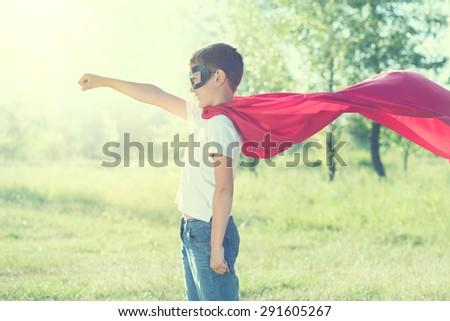 Super Hero Kid having fun outdoor. Superhero little boyover nature green blurred background
