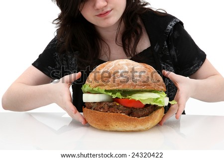 Super huge giant burger and teen girl trying to eat it.