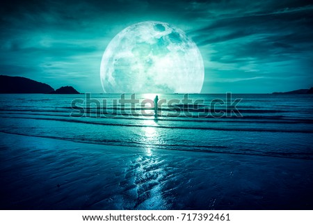 Stock Photo Super moon. Colorful sky with bright full moon over seascape and silhouette of woman standing in the sea . Serenity nature background, outdoor at gloaming. The moon taken with my own camera.
