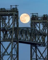 Super moon rising between Hef bridge pillars in Rotterdam evening sky