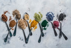 Super powders in spoons - matcha, turmeric, ginger, cocoa, spirulina, chia, cinnamon black sesame top view