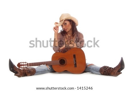 Super sexy rodeo cowgirl in torn jeans, boots and cowboy hat with a nylon string acoustic guitar - stock photo