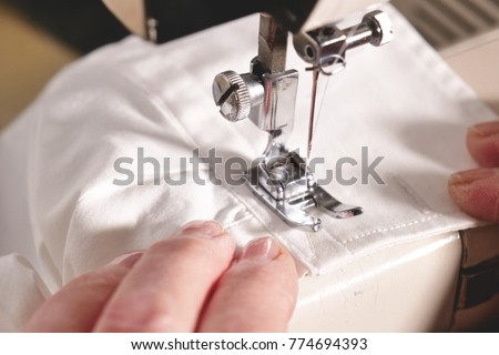 Super slow motion of a professional sewing machine stitching with white thread an Italian haute couture fabric, The seamstress sews a high fashion outfit. concept of industry, tradition, fashion #774694393