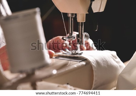 Super slow motion of a professional sewing machine stitching with white thread an Italian haute couture fabric, The seamstress sews a high fashion outfit. concept of industry, tradition, fashion #774694411