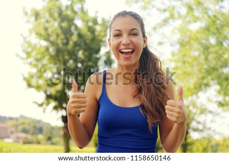 Super woman! Portrait of winner girl showing thumbs up. Positive smiling fitness woman outdoor.