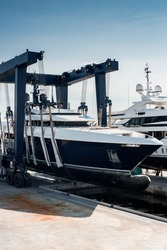 Super Yacht hauled out in shipyard, being lifted by industrial crane for refit or maintenance yard period