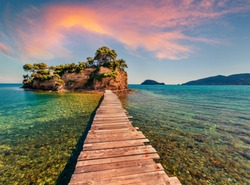 Superb summer sunrise on Port Sostis, Zakinthos island, Greece, Europe.  Wooden footbridge to Cameo Island. Beauty of nature concept background.