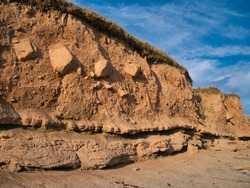 Superficial coastal deposits formed of layers of soft, eroded blown sand with rocky deposits - taken at Seahouses on the Northumberland coast on a sunny day with a blue sky.