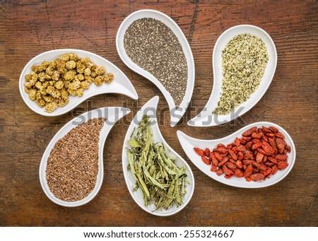 superfood samples  (mulberry, chia seeds, hemp seeds, goji berry, stevia leaf, flax seed) in teardrop shaped bowls against grunge wood