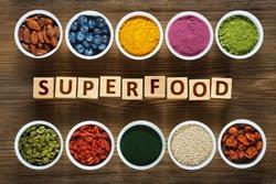 Superfoods as acai powder, turmeric, matcha green tea, spirulina, quinoa, pumpkin seeds, blueberry, dried goji berries, cape gooseberries (physalis peruviana), raw cocoa, hemp seeds on wooden table