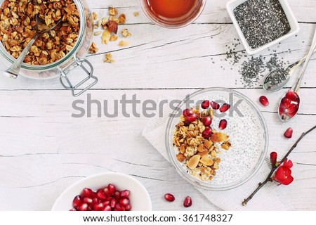 Superfoods concept : overnight chia pudding with homemade granola,pomegranate  and honey. Healthy eating. Selective focus.