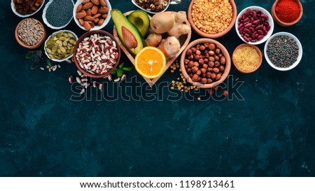 Superfoods Healthy food. Nuts, berries, fruits, and legumes. On a black stone background. Top view. Free copy space. #1198913461