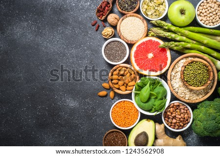 Superfoods on black stone background. Organic food and healthy vegan food. Legumes, nuts, seeds, fruit and vegetables. Top view copy space. #1243562908