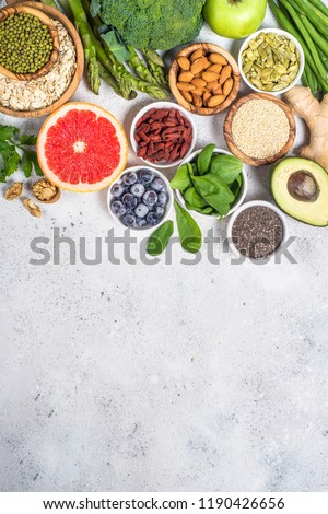 Superfoods on light stone background. Organic food and healthy vegan food. Legumes, nuts, seeds, avocado and green peas, asparagus. Top view copy space. #1190426656