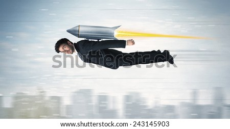 Superhero business man flying with jet pack rocket above the city concept #243145903