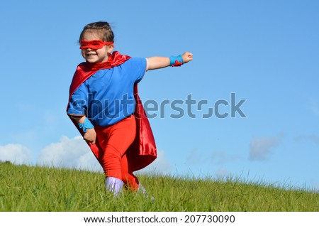 Superhero child (girl) try to fly in gree field against dramatic blue sky background with copy space. concept photo of Super hero, girl power, play pretend, childhood, imagination.