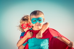 Superhero children against summer sky background. Kids having fun outdoors. Boy and girl playing. Success and winner concept