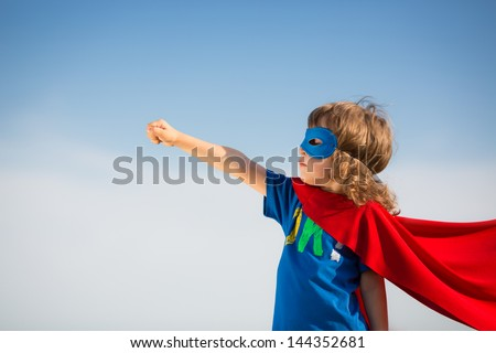 Superhero kid against blue sky background. Girl power concept
