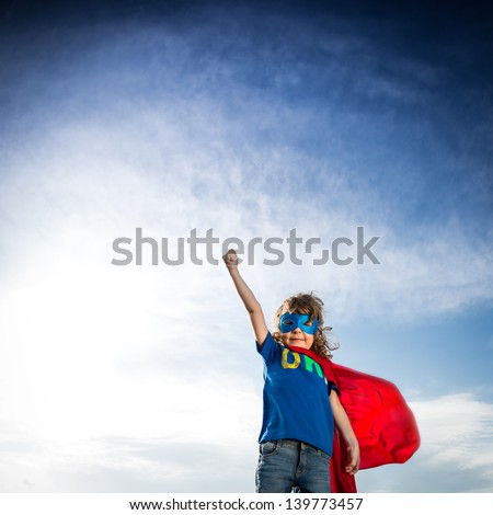 Superhero kid against dramatic blue sky background #139773457