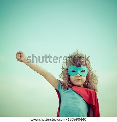 Stock Photo Superhero kid against summer sky background. Girl power and feminism concept